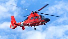 Roter Rettungshubschrauber, der in blauen Himmel sich bewegt Lizenzfreies Stockbild