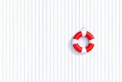 Roter Rettungsring auf einer weißen hölzernen Plankenwand, Sommerkonzept, Hintergrund Lizenzfreies Stockbild