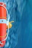 Roter Rettungsring mit blauem Meerwasser Lizenzfreies Stockfoto
