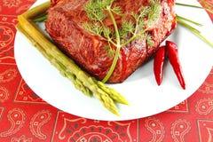 Roter Rindfleischklumpen auf Blau Stockbild