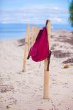 Roter Rucksack am Zaun auf exotischem tropischem Strand Lizenzfreie Stockfotos