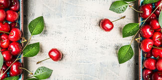 Roter süße Kirschhintergrund mit Grün verlässt auf weißem hölzernem Weinlesehintergrund, Draufsicht Stockfotos