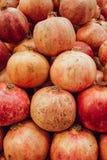 Roter Saftgranatapfel auf dunklem Hintergrund die offene Frucht eines Granatapfels liegt auf einem Hügel von Granatäpfeln stockbild
