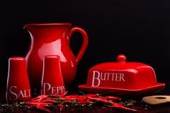 Roter Salzkeller, Pfefferkasten, Butter und Pitcher stellten auf dunklen Hintergrund durch Cristina Arpentina ein Lizenzfreie Stockfotos