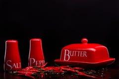 Roter Salzkeller, Pfefferkasten und Butter auf dunklem Hintergrund durch Cristina Arpentina lizenzfreie stockfotografie