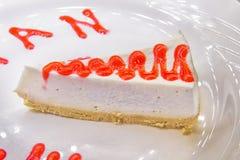 Roter Samt-Kuchen geschnitten im Stück auf weißer Platte über roter Platzmatte Roter Kuchen des Samts Erdbeere cake Stockbild