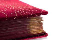 Roter Samt mit den goldenen Buchseiten lokalisiert auf weißem Hintergrund lizenzfreie stockfotos