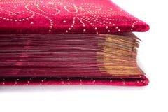 Roter Samt mit den goldenen Buchseiten lokalisiert auf weißem Hintergrund lizenzfreie stockbilder