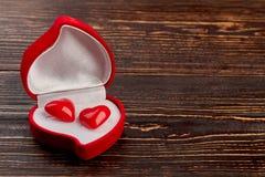 Roter Samtkasten mit geformten Ohrringen des Herzens stockfotos