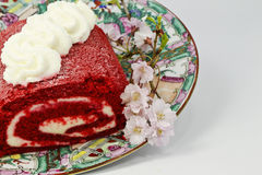 Roter Samtrollenkuchen und rosafarbene Blüten Stockbild