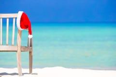 Roter Sankt-Hut auf Strandstuhl an den tropischen Ferien Stockfotos