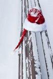 Roter Santa Claus-Hut auf Schnee bedeckte Bank Stockfoto