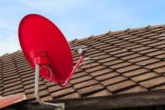 Roter Satellitenfernsehen-Empfänger-Teller auf dem alten Fliesen-Dach Stockfoto