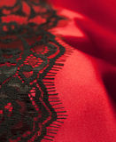 Roter Satin mit schwarzer Spitze Stockbild