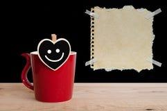 Roter Schalenkaffee mit Lächeln auf Herzbrett und braunes Papier mit Lochstreifen auf Tafel und hölzernem Hintergrund Stockfoto