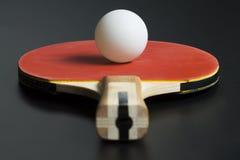 Roter Schläger des Tischtennis und weißer Tischtennisball Stockfotografie