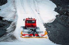 Roter Schneepflug, der die Bahn am Skiort Hintertux, Österreich klärt Stockfoto