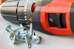 Roter Schraubenzieher und Schrauben für Metallnahaufnahme Stockfotos