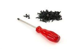 Roter Schraubenzieher und schwarze Schraube Stockfoto