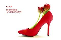 Roter Schuh des hohen Absatzes der Damen mit Tulpen nach innen, auf Weiß, Stockbilder