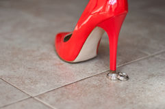 Roter Schuh und Eheringe Stockfotos