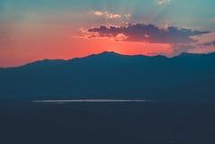 Roter Sonnenuntergang über bewölkten Bergen Stockbilder