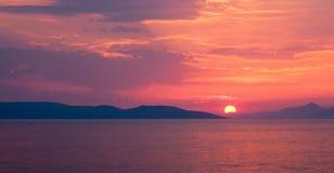 Roter Sonnenuntergang über dem Meer mit Sonne zwischen Hügeln, Panorama Stockbild