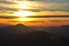 Roter Sonnenuntergang in den Bergen mit Wolken Lizenzfreie Stockfotos