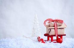 Roter Spielzeugschlitten mit einem Stapel von Geschenken, Weihnachtenbal Lizenzfreie Stockfotos