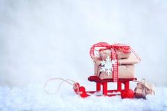 Roter Spielzeugschlitten mit einem Stapel von Geschenken, Weihnachtsball, Schneeflocke Stockbilder