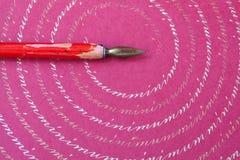 Roter Spitzenstift auf rosa Papier maserte Hintergrund, abstraktes Buchstabemuster Makroansicht, flache Schärfentiefe Lizenzfreies Stockfoto