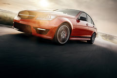 Roter Sportwagen-schnelle Antriebs-Geschwindigkeit auf Asphalt Road Lizenzfreie Stockbilder