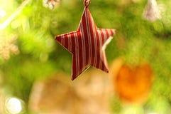 Roter Stern hängt am Weihnachtsbaum Bokeh Hintergrund Weihnachten verzierte Baum Lizenzfreie Stockbilder
