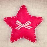Roter Stern mit hölzernem Knopf und Bogen auf Weinlesegewebe Stockfotos