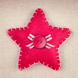 Roter Stern mit hölzernem Knopf und Bogen auf Weinlesegewebe tauchen auf Stockfotos