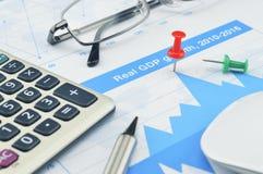Roter Stift mit Stift, Taschenrechner und Gläsern auf Finanzdiagramm, Teer Lizenzfreies Stockfoto