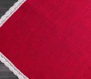 roter Stoff mit weißes Leinen gesponnener handgemachter Spitze Stockfotografie