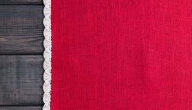 roter Stoff mit weißes Leinen gesponnener handgemachter Spitze Stockbild