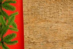 Roter Stoff mit Weihnachtsbaumast über hölzerner Beschaffenheit Stockbilder