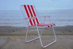 Roter Strandstuhl auf dem Sandstrand Stockfotografie
