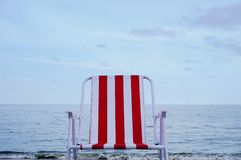 Roter Strandstuhl auf dem Sandstrand Stockfotos