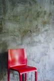 Roter Stuhl auf Betonmauerhintergrund Lizenzfreies Stockfoto