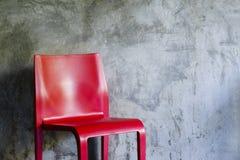 Roter Stuhl auf Betonmauerhintergrund Stockbilder