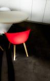 Roter Stuhl auf einem schwarzen Teppich und einer weißen Tabelle Stockbilder