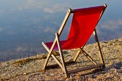 Roter Stuhl auf einer Bank von Ada See mit Wolkenreflexionen in einem Wasser am Sommermorgen, Belgrad Stockfotografie