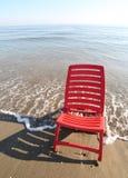 Roter Stuhl wird durch das Meer gebadet Lizenzfreies Stockfoto