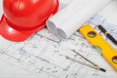 Roter Sturzhelm, Bauentwürfe und Werkzeuge Stockfotografie