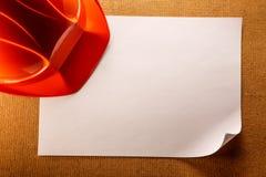 Roter Sturzhelm und leeres Papier Lizenzfreie Stockfotos