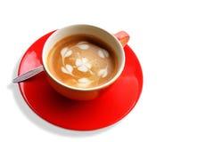 Roter Tasse Kaffee mit Herzen und Blume gemalt auf Schaum Stockfotos