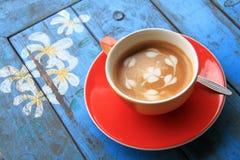 Roter Tasse Kaffee mit Herzen und Blume gemalt auf Schaum Stockbild